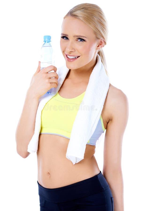 Sportliche blonde Frau, die mit Wasserflasche aufwirft lizenzfreie stockfotos