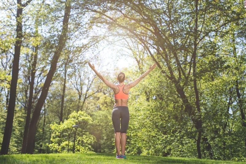 Sportliche Dame grüßt Sonne in der Natur stockbilder