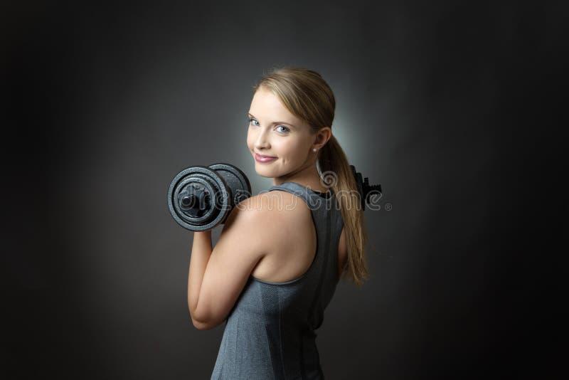 Sportliche Frau auf grauem Hintergrund mit Dummköpfen lizenzfreie stockfotos