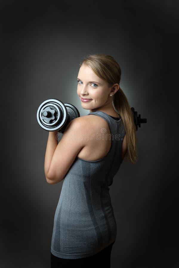 Sportliche Frau auf grauem Hintergrund mit Dummköpfen lizenzfreie stockfotografie