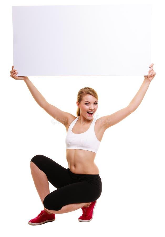 Sportliche Frau der Eignung, die leere leere Anzeigenfahne hält lizenzfreies stockfoto