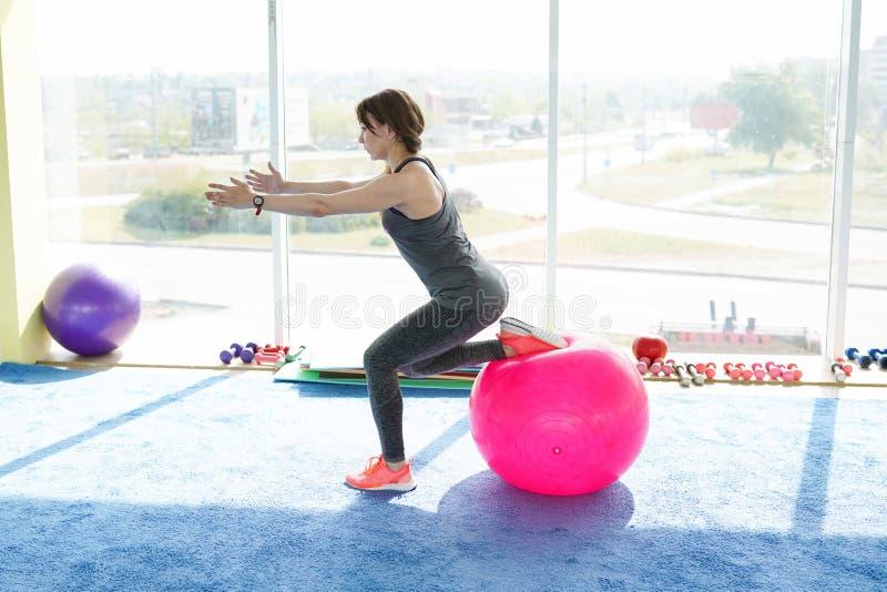 Sportliche Frau, die Übungen mit geeignetem Ball in der Turnhalle tut Konzept: Lebensstil, Eignung, Aerobic und Gesundheit lizenzfreie stockfotos