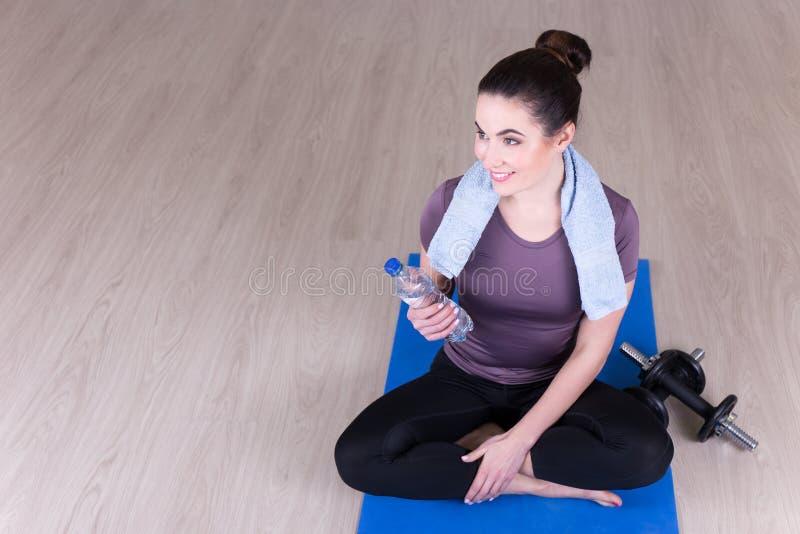 Sportliche Frau, die auf Bretterboden nach der Ausbildung sitzt lizenzfreies stockfoto