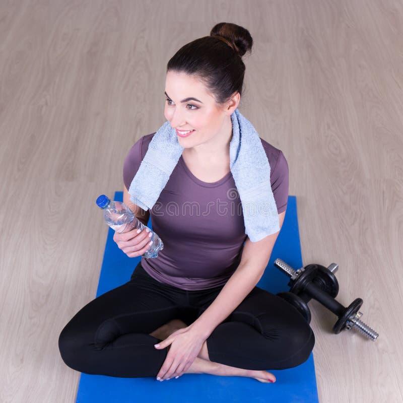 Sportliche Frau, die auf dem Boden nach der Ausbildung sitzt stockbild
