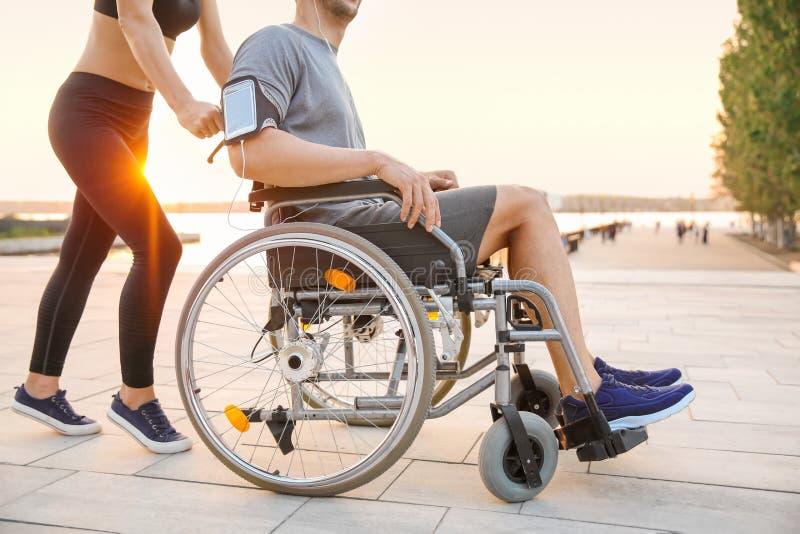 Sportliche Frau, die draußen jungem Mann im Rollstuhl hilft lizenzfreie stockbilder