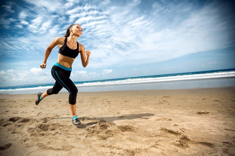 Sportliche Frau, die durch das Meer auf Strand läuft lizenzfreie stockfotos