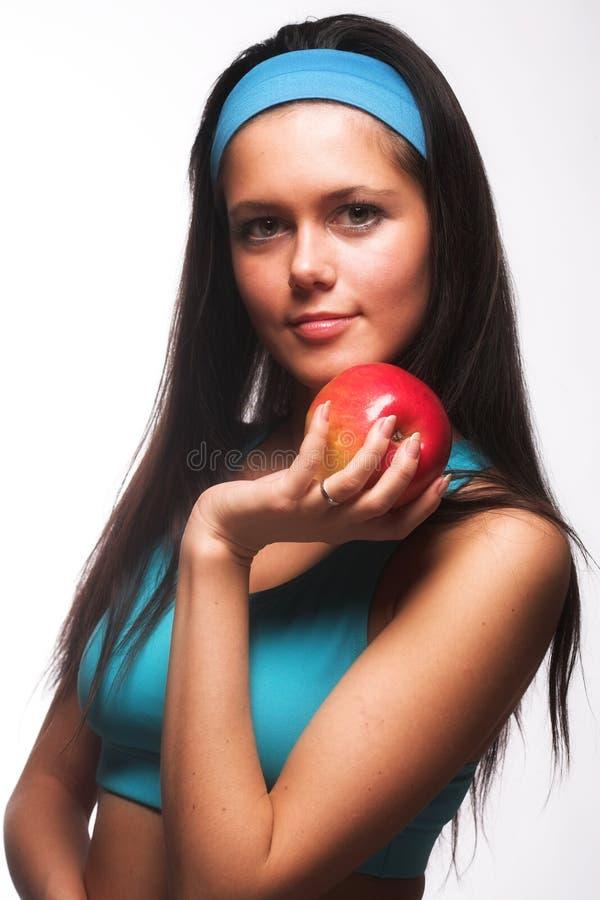 Sportliche Frau, die einen roten Apfel beißt stockfoto