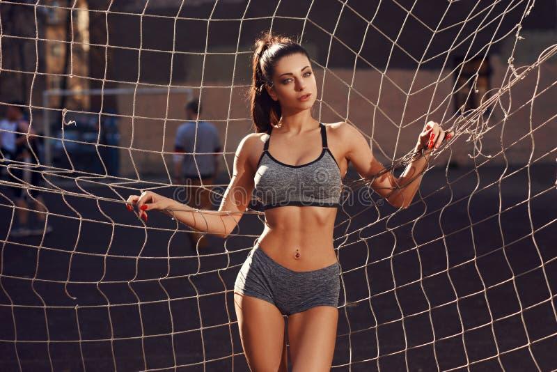 Sportliche Frau, die gegen Fußballnetz aufwirft stockfotografie