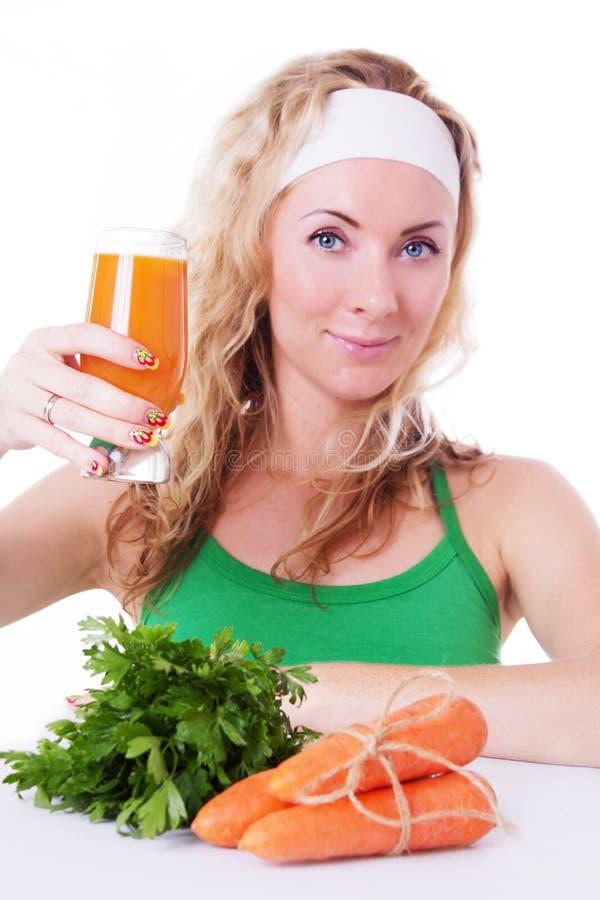 Sportliche Frau, die Karottensaft und Grüns hält lizenzfreies stockbild