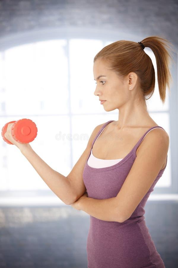 Sportliche Frau, die mit Dumbbell trainiert stockfotos