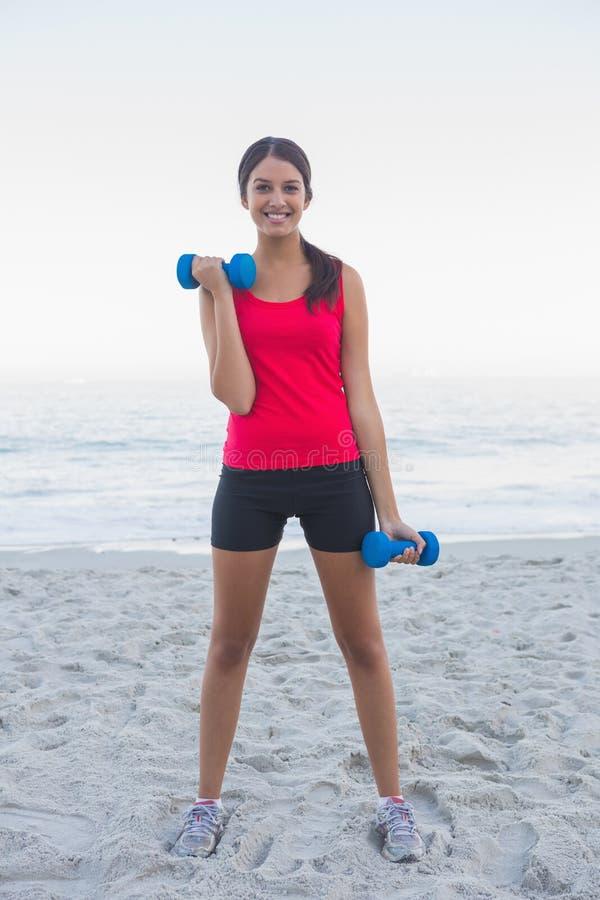 Sportliche Frau, die mit Dummköpfen trainiert lizenzfreies stockbild