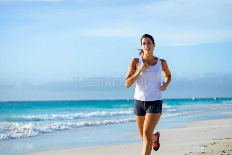 Sportliche Frau, die am tropischen Strand läuft stockfotografie