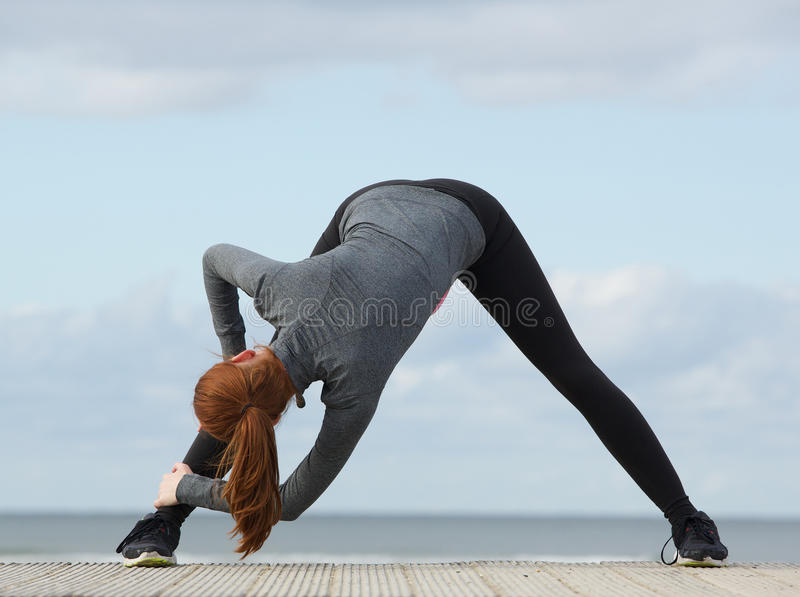 Sportliche Frau, die unten verbiegt und Übung ausdehnt stockfotografie