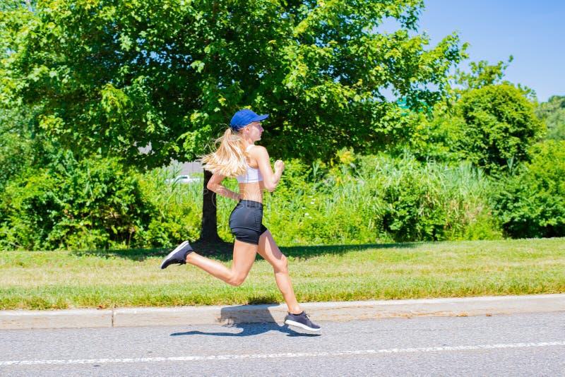 Sportliche Frau im Sportkleidungshinterbetrieb auf der Straße Athletenmädchen rüttelt im Park lizenzfreie stockfotos