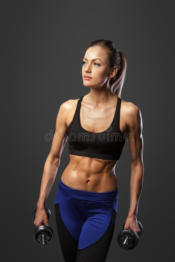 Sportliche Frau tut die Übungen mit Dummköpfen stockbild
