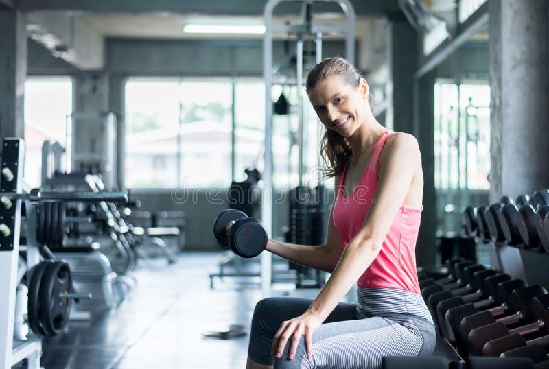 Sportliche Frauenübung mit Dummkopf, Frau in der Sportkleidung tut die Übungen an der Turnhalle lizenzfreies stockbild