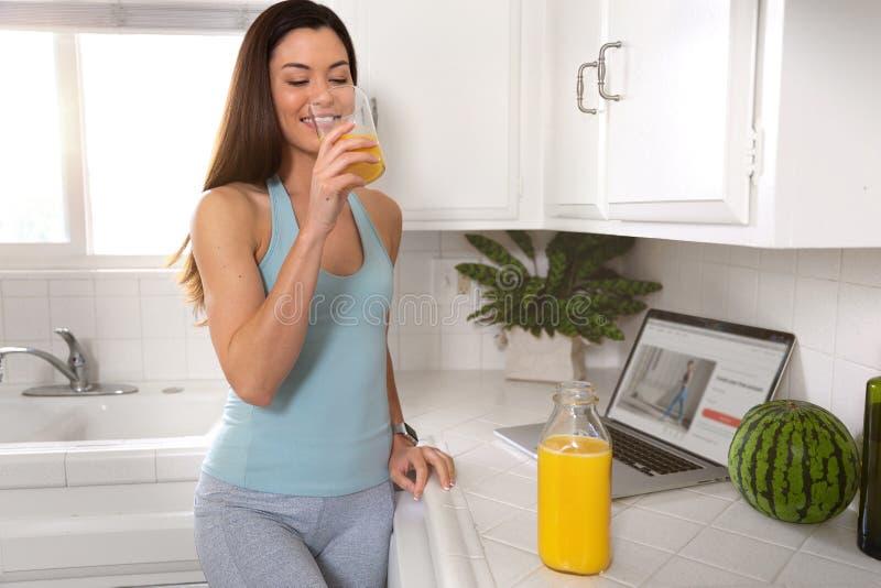 Sportliche geeignete Frau, die morgens frisches Glas Orangensaft, gesunder Lebensstil, Eignung, Übung, Wellness trinkt lizenzfreies stockfoto