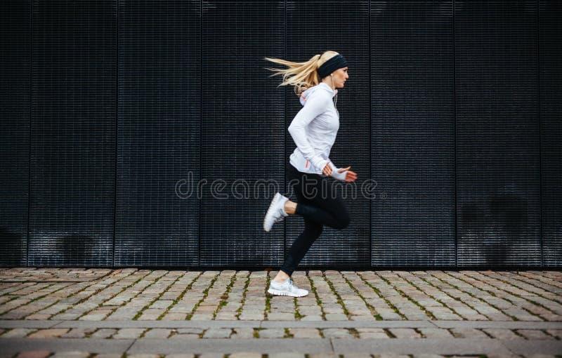 Sportliche junge Frau, die auf Bürgersteig am Morgen läuft stockbilder