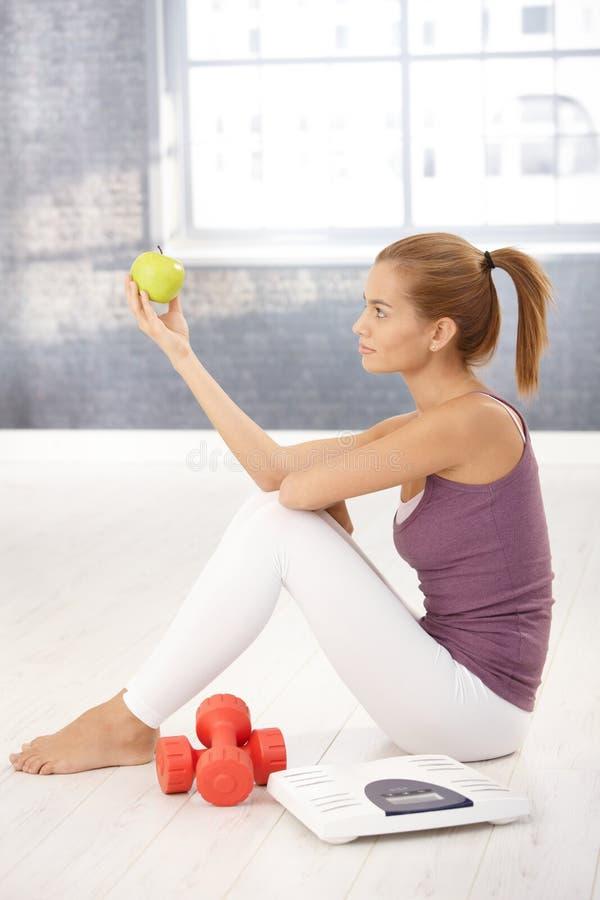 Sportliche junge Frau, die mit Apfel aufwirft stockbild