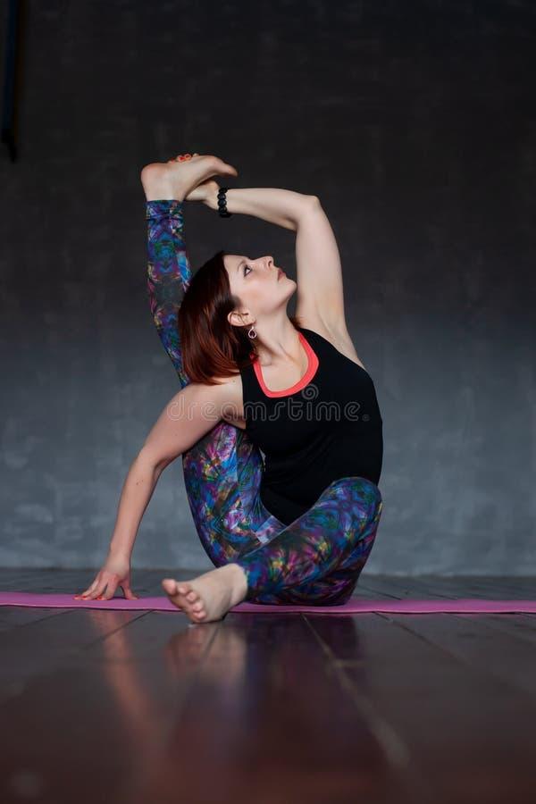 Sportliche junge Frau, die Parivritta Kraunchasana, Drehreiher, Kompass-Haltung tut lizenzfreie stockfotografie