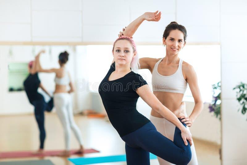 Sportliche junge Frau, die Yogahaltung Natarajasana Königs Dancer mit Lehrertrainer an der roten Yogamatte in der Trainingsklasse lizenzfreie stockbilder