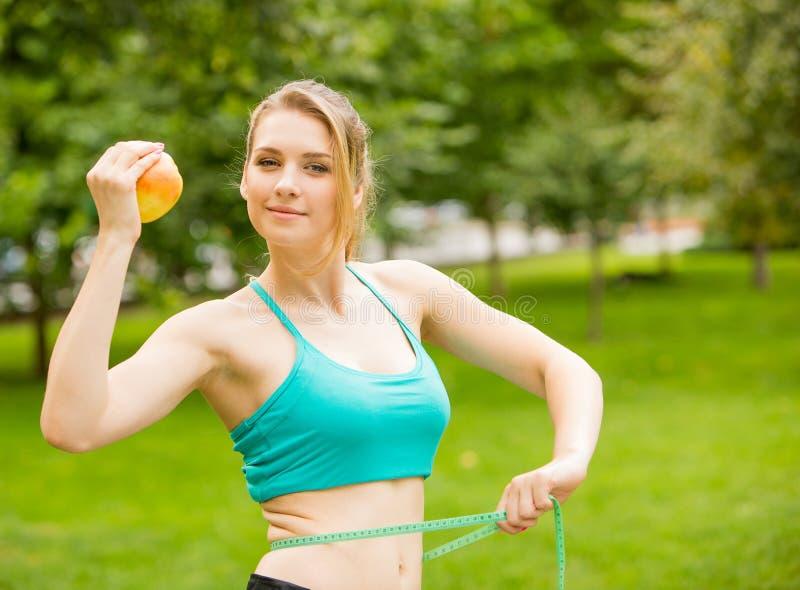 Sportliche junge Frau mit Apfel und messendem Band lizenzfreies stockbild