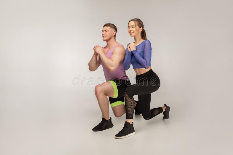 Sportliche junge Paare in der modischen bunten Sportkleidung, die Laufleine auf linkem Fuß tut lizenzfreies stockbild