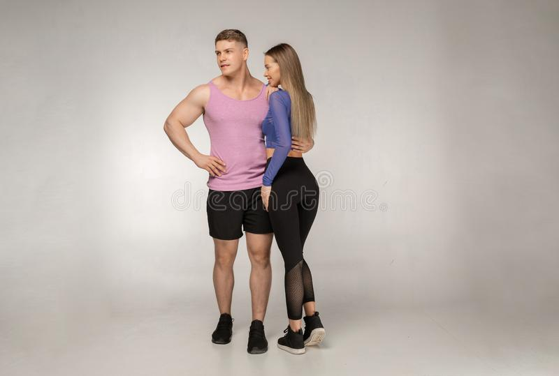 Sportliche junge Paare, die im Studio auf grauem Hintergrund aufwerfen stockfotografie