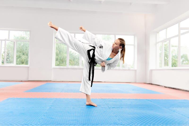 Sportliche Karatefrau gegen das große Fenster, das in Karateposition steht stockfoto