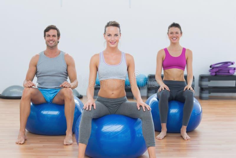Sportliche Leute, die auf Übungsbällen an der Turnhalle sitzen lizenzfreies stockfoto