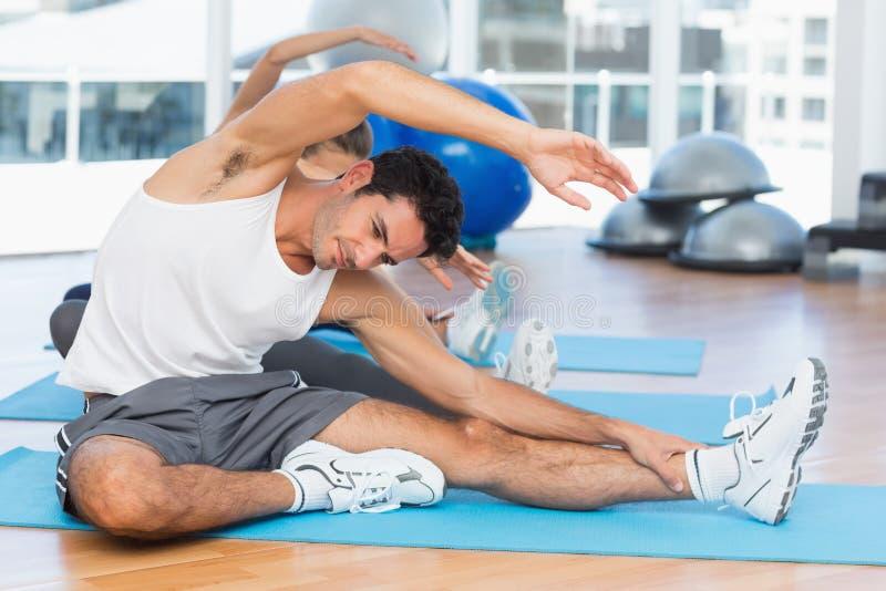 Sportliche Leute, die Hände an der Yogaklasse ausdehnen lizenzfreie stockbilder