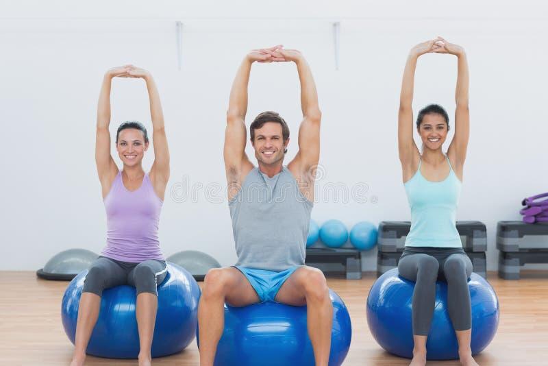 Sportliche Leute, die herauf Hände auf Übungsbällen an der Turnhalle ausdehnen lizenzfreies stockfoto