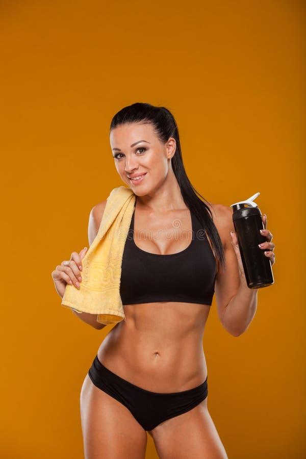 Sportliche muskulöse Frau mit Wasser, lokalisiertes Gelb lizenzfreie stockfotografie