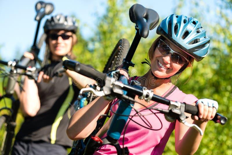Sportliche Paare, die ihre Mountainbiken tragen lizenzfreie stockbilder