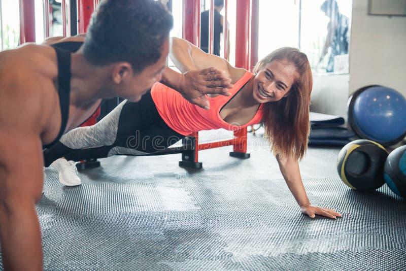 Sportliche Paare, die miteinander Hoch fünf geben, beim Handeln hochdrücken Sie stockfoto
