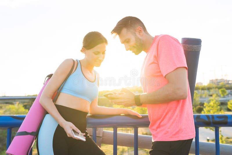 Sportliche Paare, die nachdem dem Trainieren unter Verwendung des Handys stillstehen stockfotos