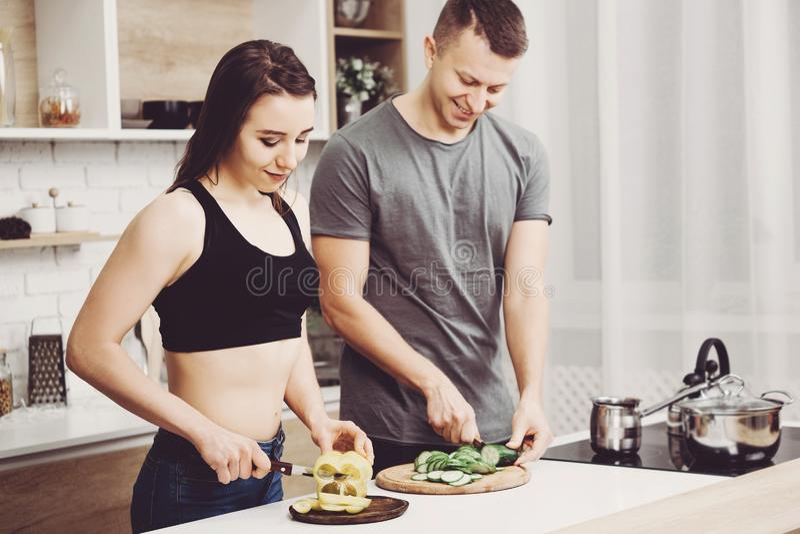 Sportliche Paare, die zusammen gesunde Nahrung kochen stockfotos