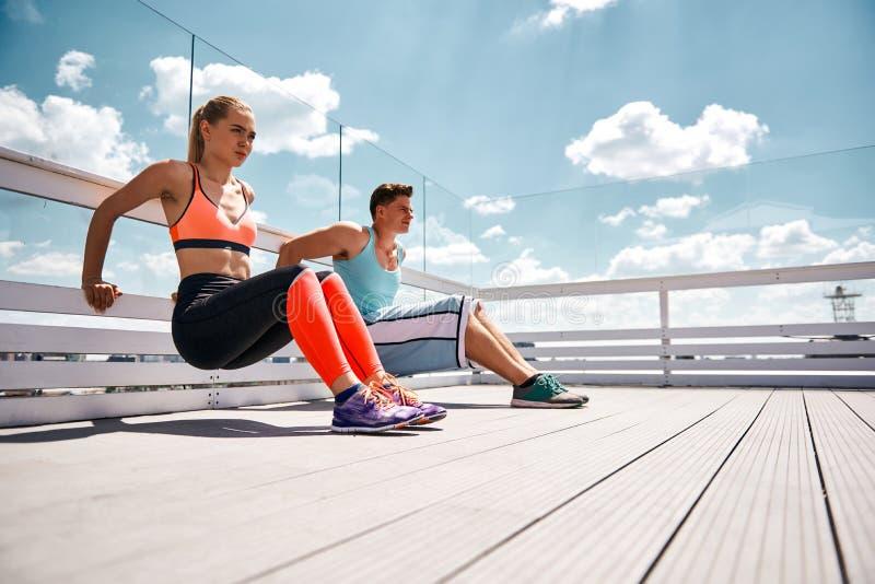 Sportliche Paare tun Trizeps StoßUPS auf städtischer Terrasse stockfotografie