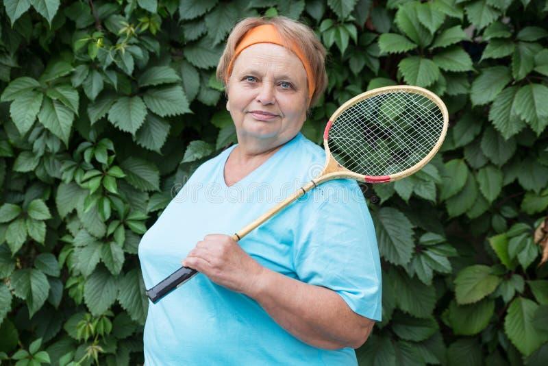 Sportliche Pensionärfrau mit Schläger stockfotografie