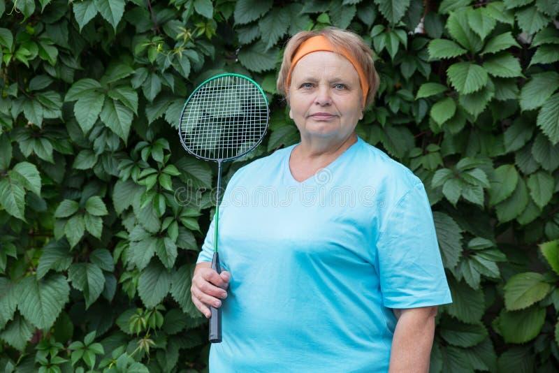 Sportliche Pensionärfrau mit Schläger lizenzfreie stockfotografie