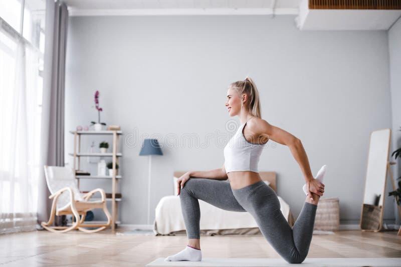 Sportliche Schönheit, die zu Hause trainieren ausdehnt lizenzfreies stockbild