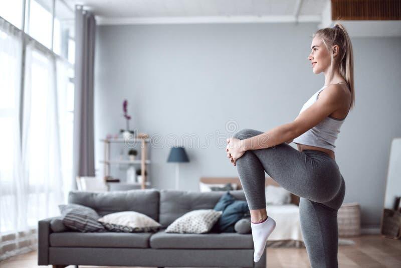 Sportliche Schönheit, die zu Hause trainiert, um geeignet zu bleiben lizenzfreie stockfotografie