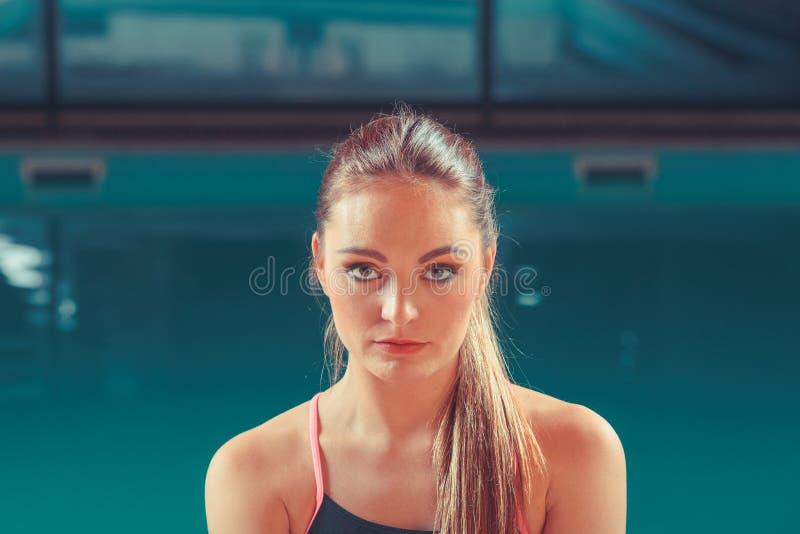 Sportliche Sitzfrau an Swimmingpool-Rand Poolside stockbilder