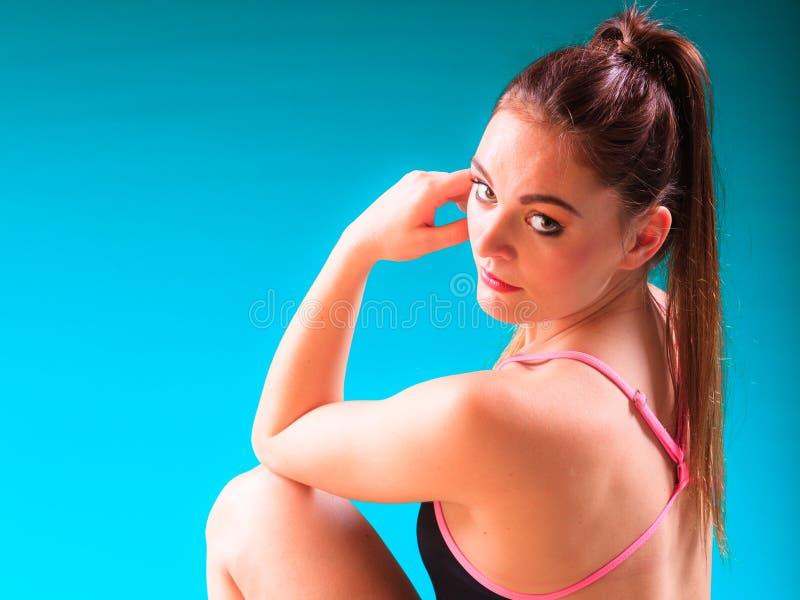 Sportliche Sitzfrau an Swimmingpool-Rand Poolside stockfotografie