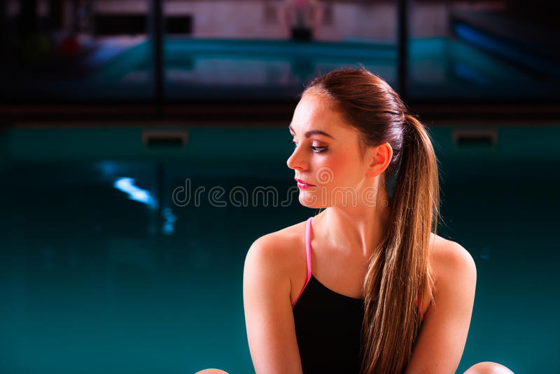 Sportliche Sitzfrau an Swimmingpool-Rand Poolside lizenzfreie stockbilder