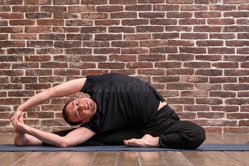 Sportlicher attraktiver junger ausarbeitender Mann, Yoga, pilates, Eignungstraining, asana Parivrtta Janu Sirsasana über Backstei lizenzfreies stockbild