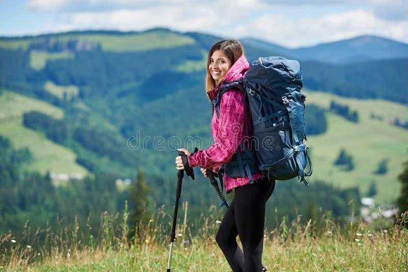 Sportlicher Frauentourist mit Rucksack und Trekking haftet das Wandern in den Bergen lizenzfreie stockfotos