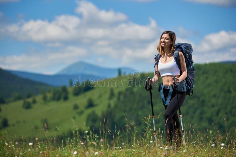 Sportlicher Frauentourist mit Rucksack und Trekking haftet das Wandern in den Bergen stockfotos