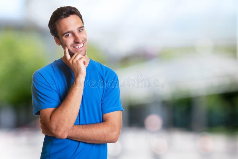 Sportlicher hispanischer Mann mit Bart lächelnd an der Kamera stockfotografie