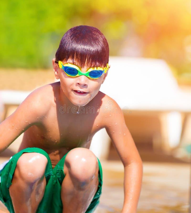 Sportlicher Junge, der in das Pool springt stockbilder